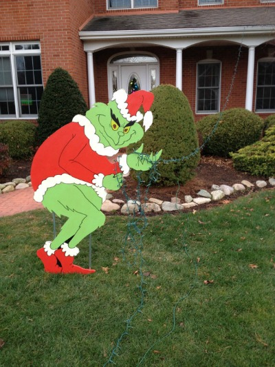 giant grinch stealing lights off house